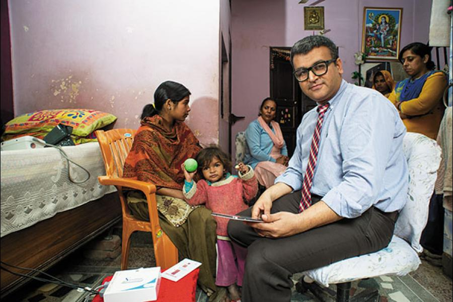 Kanav Kahol conducts diagnostic tests on the Swasthya Slate at a patient's house in Delhi